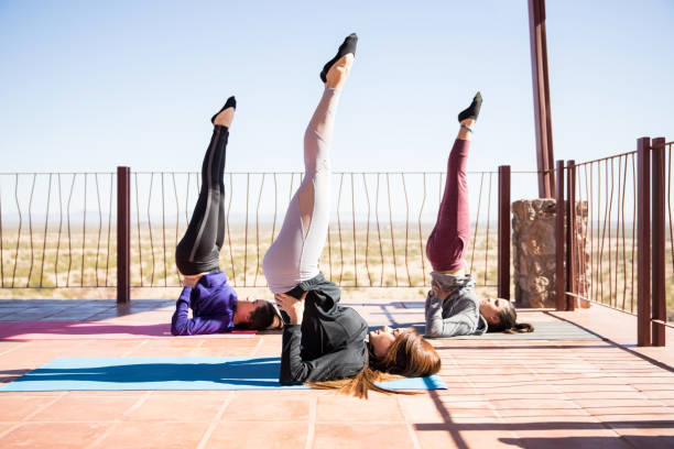 Shoulder stand in yoga class Three young women standing on their back and shoulder at health center shoulder stand stock pictures, royalty-free photos & images