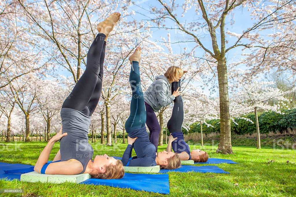 Shoulder stand practised by yoga group stock photo