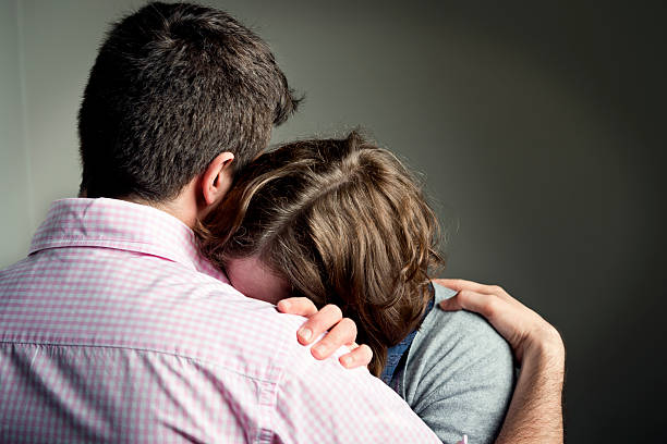 shoulder to cry on - grief stock photos and pictures