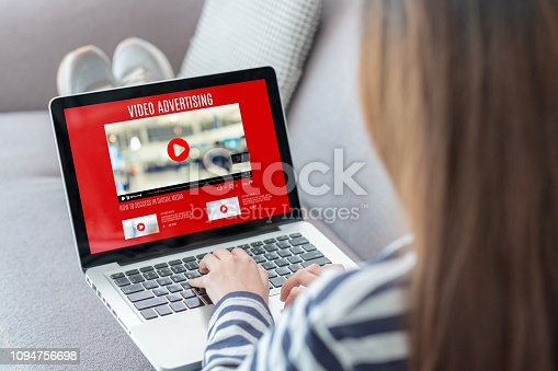 1125605742istockphoto Shoulder view of woman watching video online with advertising on laptop computer on sofa at home.viral influencer media concept. 1094756698