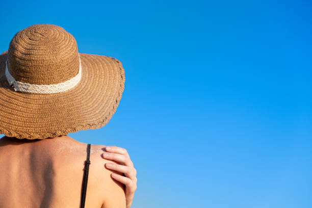 Shoulders of a young woman in a retro hat, chot from behind stock photo