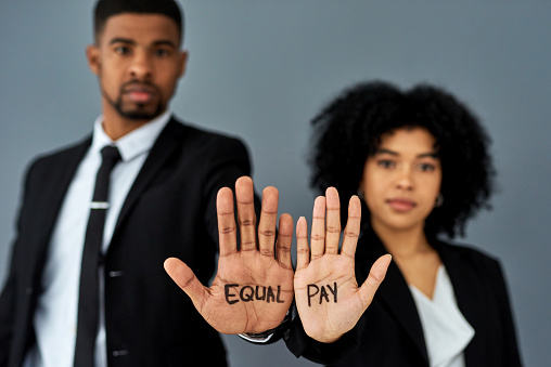 Shot of a businessman and businesswoman advocating for equal pay against a grey studio background