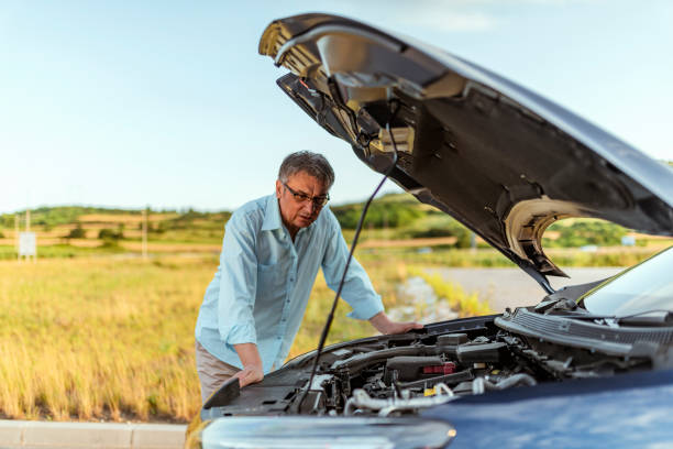 I should've insured it! Senior Man examining a broken car on a sunny day. Photo of senior businessman looking under the hood of breakdown car at outdoor. Gray hair stressed man having trouble with his broken car looking in frustration on the failed engine. aground stock pictures, royalty-free photos & images