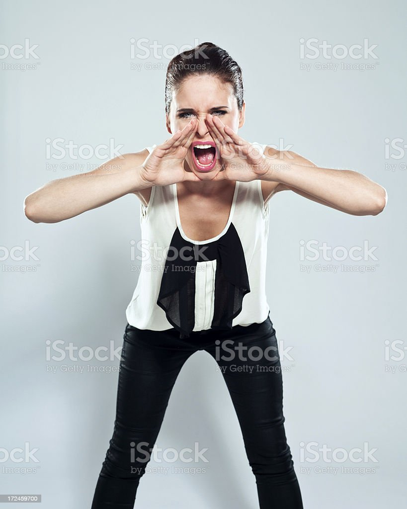 Shout Portrait of young woman shouting at the camera. Studio shot on a grey background. 20-24 Years Stock Photo