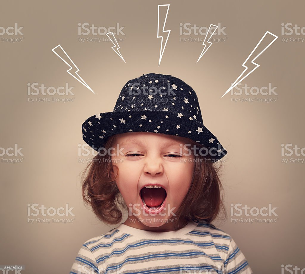 Shouting angry small kid with open mouth and lightnings above stock photo