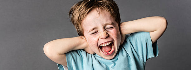 shouting child with red hair and attitude ignoring parents scolding shouting little child with red hair, freckles and an attitude ignoring parents scolding, blocking his ears with hands against domestic violence, grey background single word no stock pictures, royalty-free photos & images