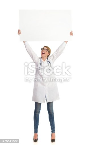 istock Shouting female doctor holding banner abover her head. 475541553