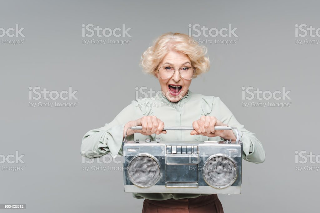 shouting senior woman with boombox isolated on grey zbiór zdjęć royalty-free