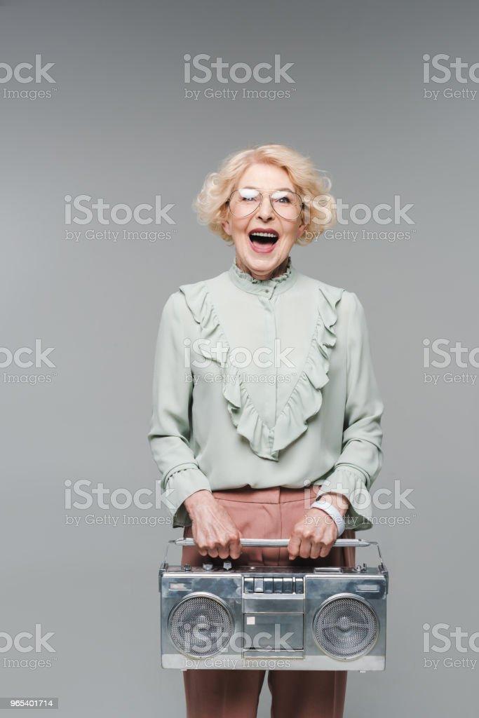 femme hauts cris avec boombox vintage isolé sur fond gris - Photo de A la mode libre de droits