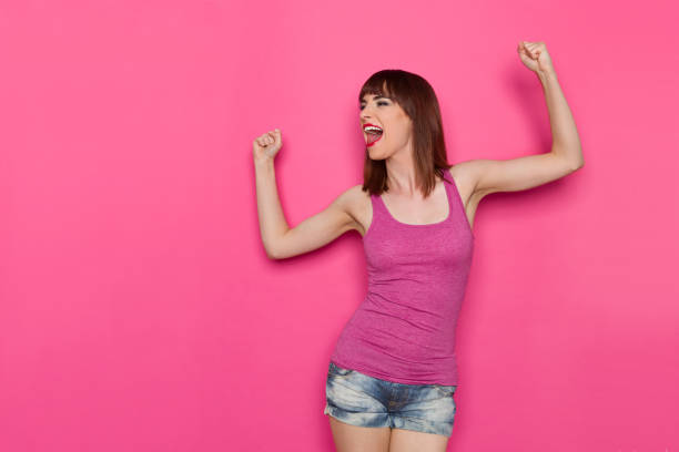 Shouting Young Woman Clenches Fists And Looking Away Young woman in pink magenta and jeans shorts is shouting and clenching fists, looking away. Three quarter length studio shot on pink background. tank top stock pictures, royalty-free photos & images