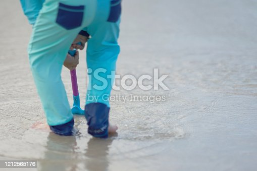 shovel holded by kid hand digging on sand and sea waterin summer vacation concept with copy space