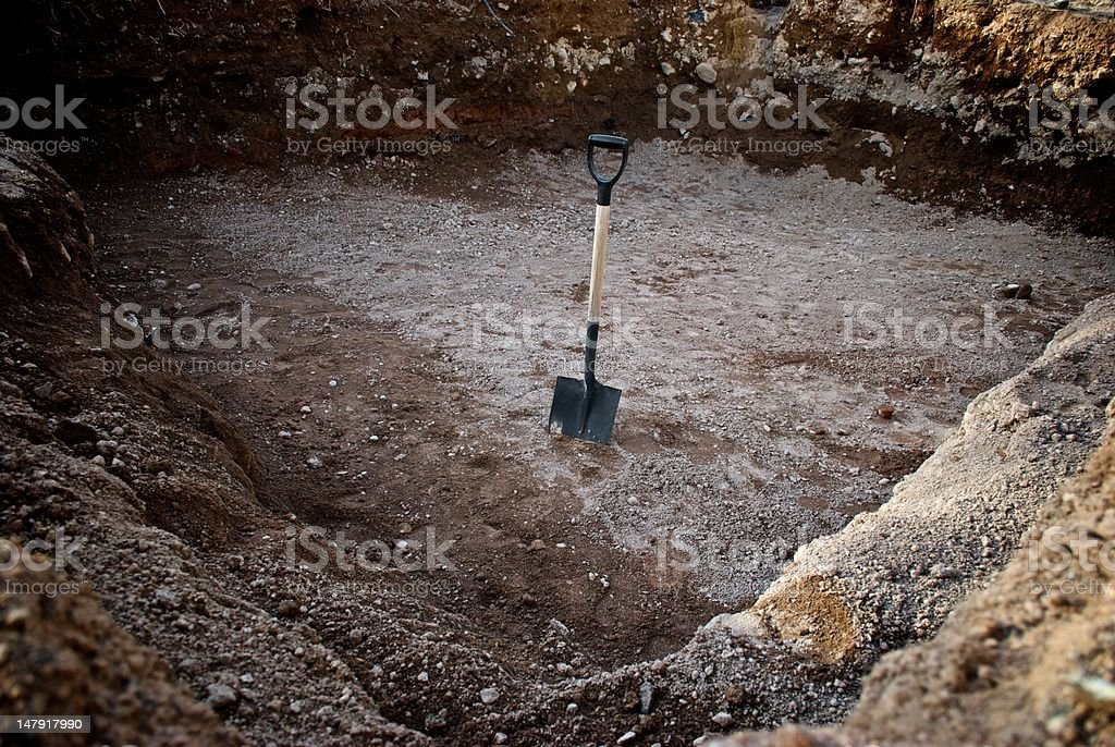 Shovel in dirt after digging a giant hole or pool stock photo