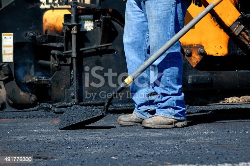 Shovel loaded with alphalt ready for paving. It is hot and ready to be spread.  The person is wearing jeans and protective boots.