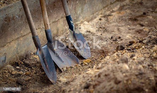 Shovel on a background of the trench close up
