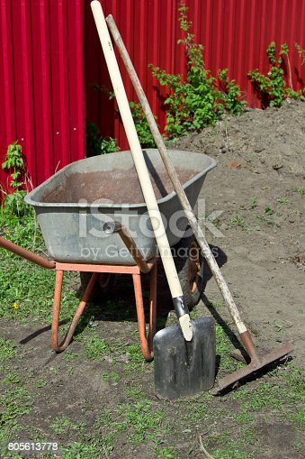 istock Shovel, rake and wheelbarrow against the red fence. 805613778
