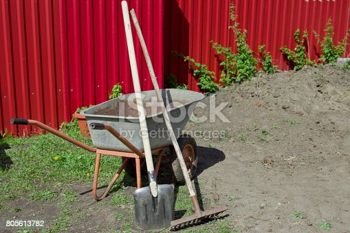 istock Shovel, rake and wheelbarrow against the red fence. 805613782