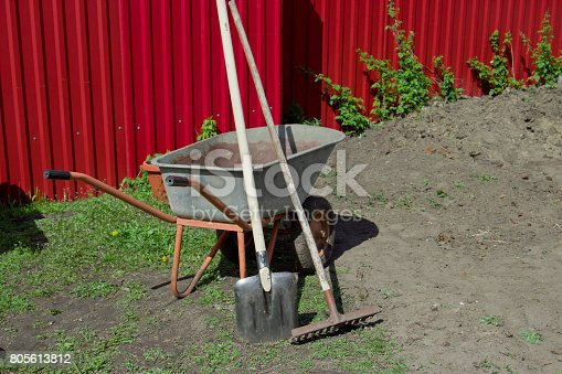 istock Shovel, rake and wheelbarrow against the red fence. 805613812