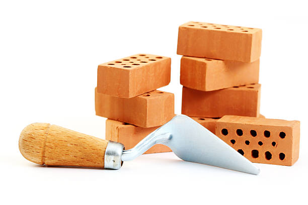 a shovel tool and several stacked bricks - construction material stock photos and pictures