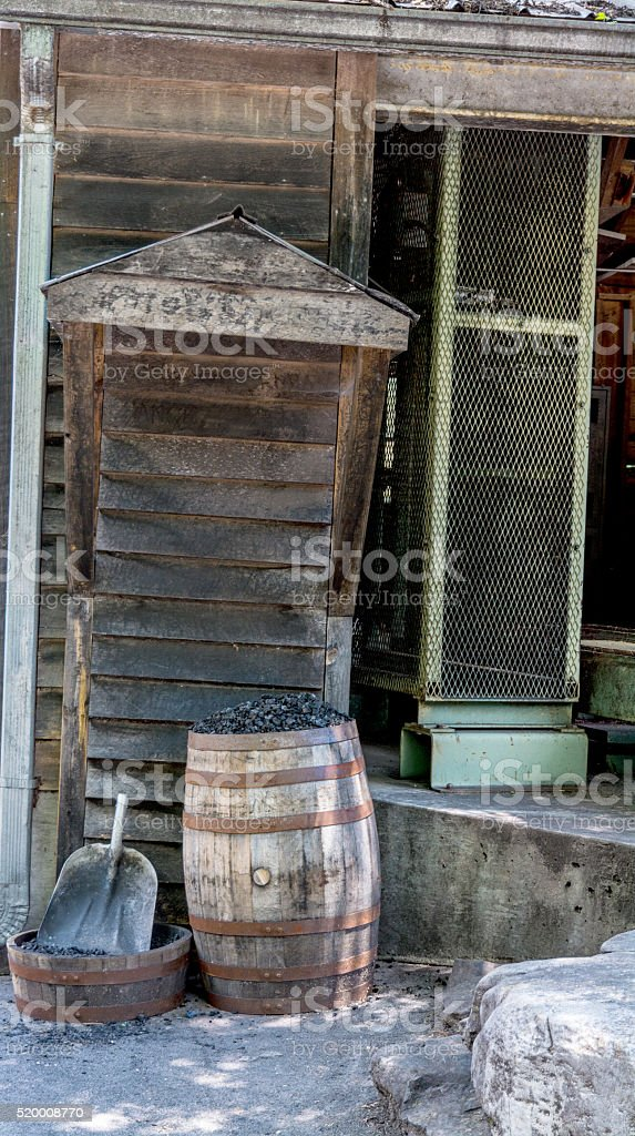 Shovel with a barrel of coal and old building stock photo