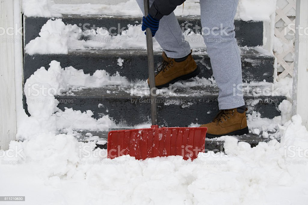 Shoveling snow in the winter Snowy gray steps being shoveled by a red shovel, man in boots Blizzard Stock Photo
