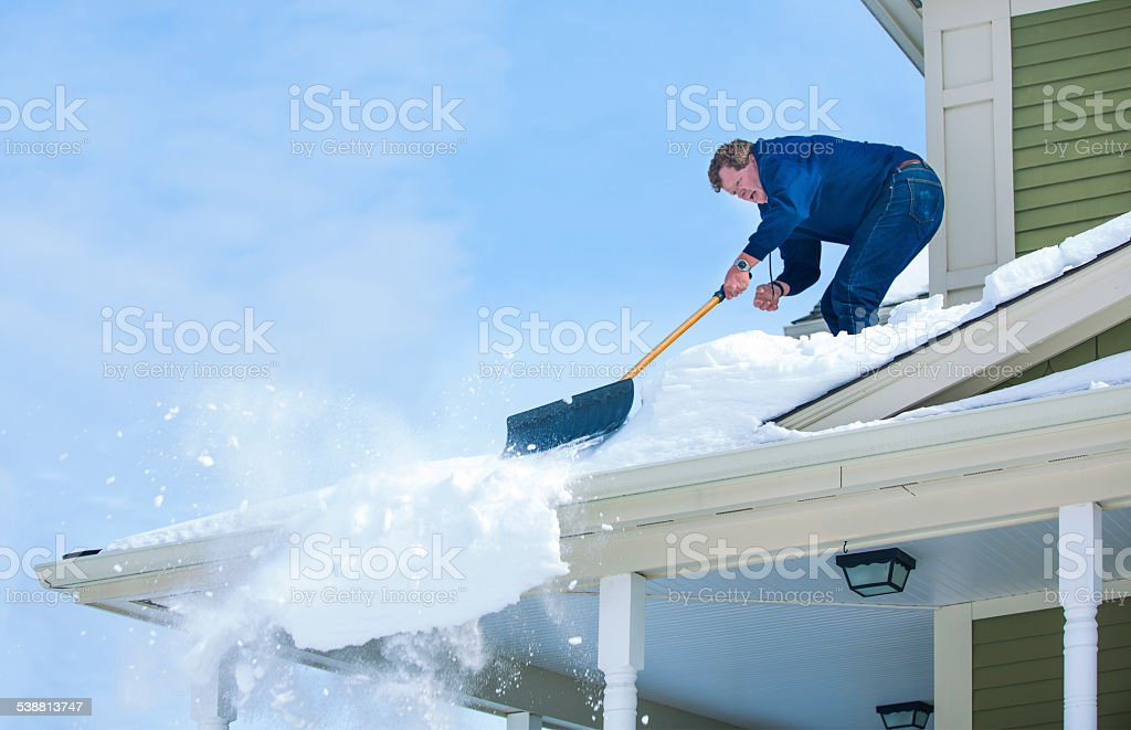 Shoveling Snow Off the Roof stock photo