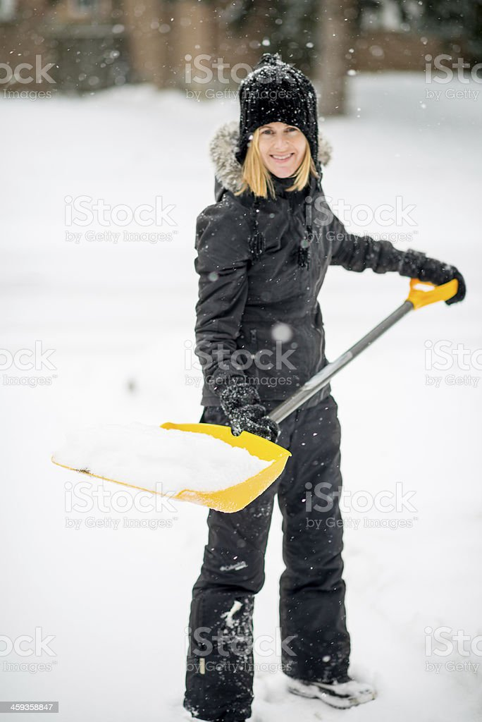 Shovelling snow off her driveway after a storm stock photo