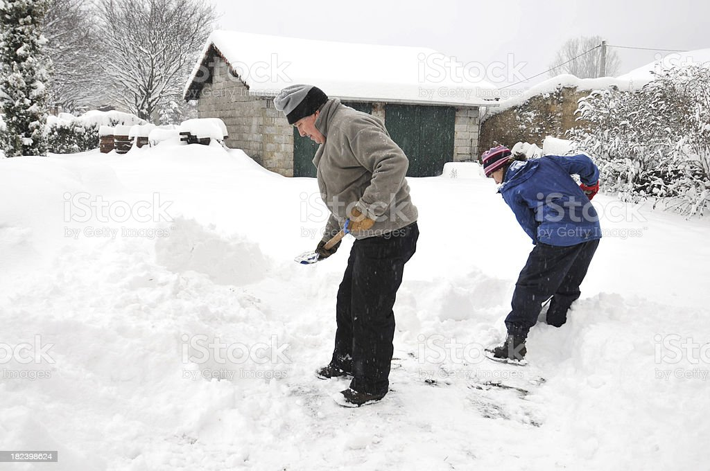Shovelling snow together stock photo