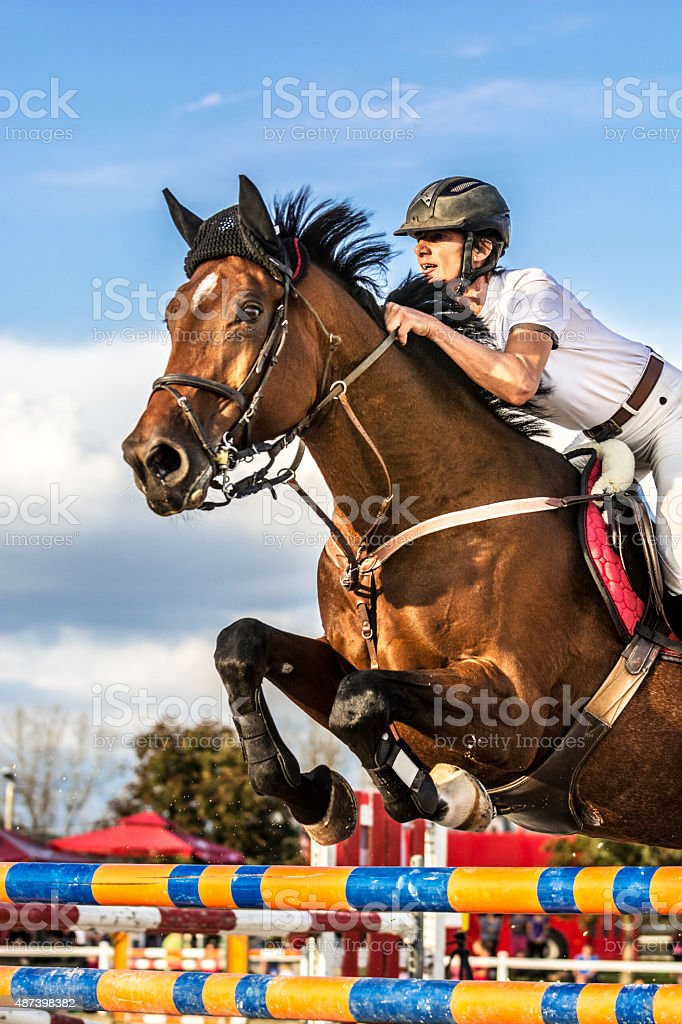 Show jumping - horse with rider jumping over hurdle stock photo