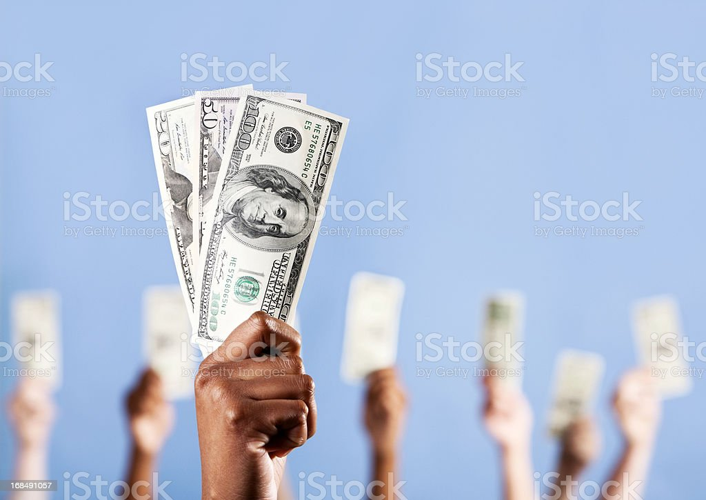 Show me the money! Many hands holding up US dollars stock photo