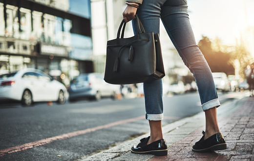 Closeup shot of a businesswoman walking with her handbag in the city