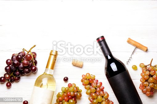 Vintage bottles of red & white wine with blank matte label, corkscrew & grapes, wood table background. Expensive bottle of cabernet sauvignon concept. Copy space, top view, flat lay