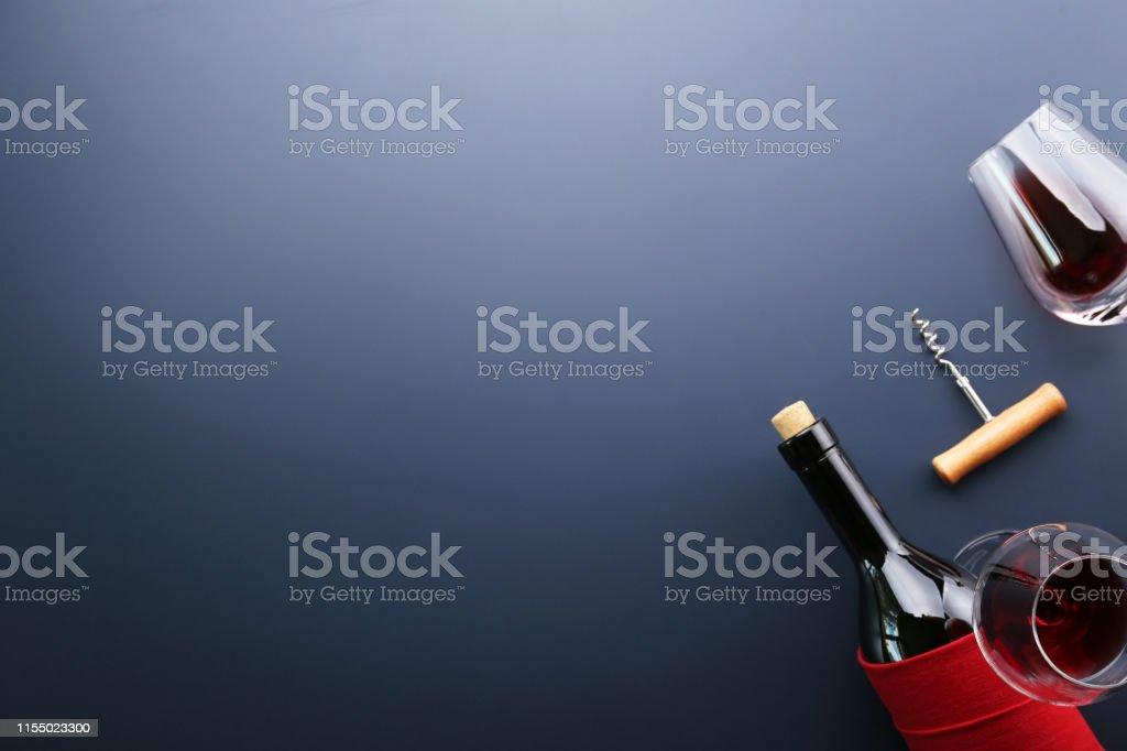 Vintage bottle of red wine with blank matte black label, corkscrew on...