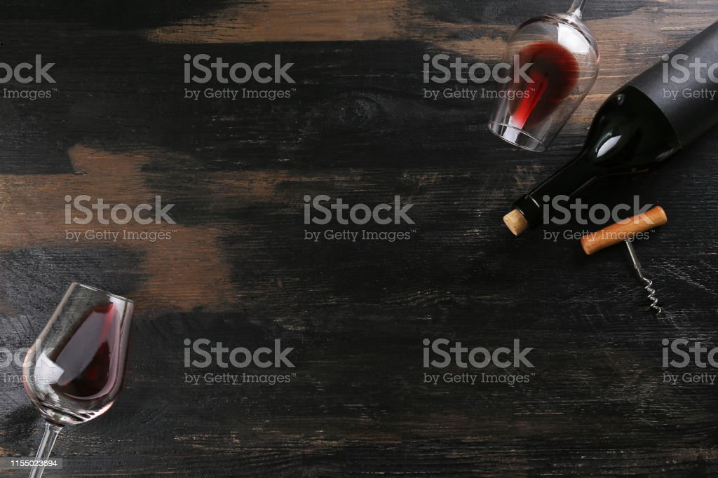 Vintage bottle of red wine with blank matte black label, poured...