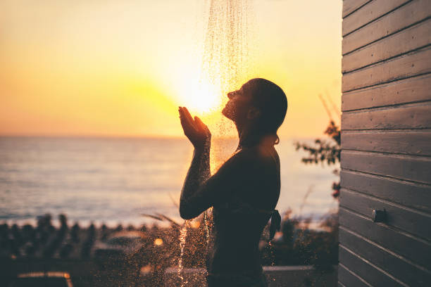 dusche bei sonnenuntergang - sonnendusche stock-fotos und bilder