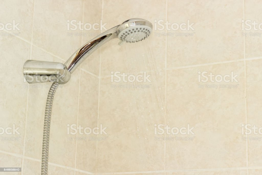 Shower head in holder on wall with beige tiles stock photo