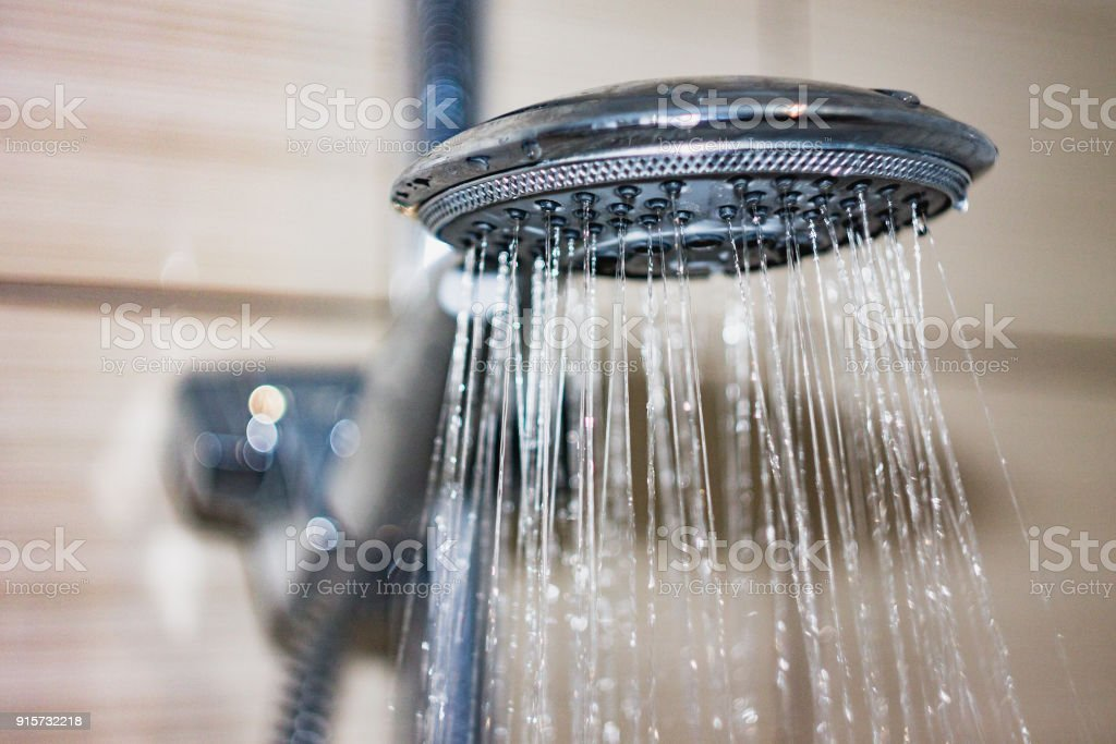 shower head with drops of water falling down stock photo
