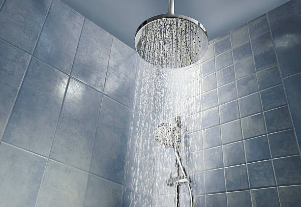 Shower head with running water Low angle of running water from shower head in a cool coloured shower household fixture stock pictures, royalty-free photos & images