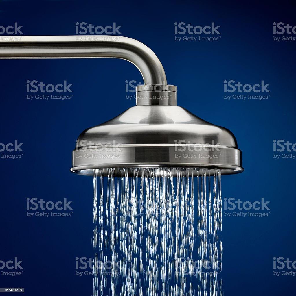 Shower head with streaming water, blue background stock photo