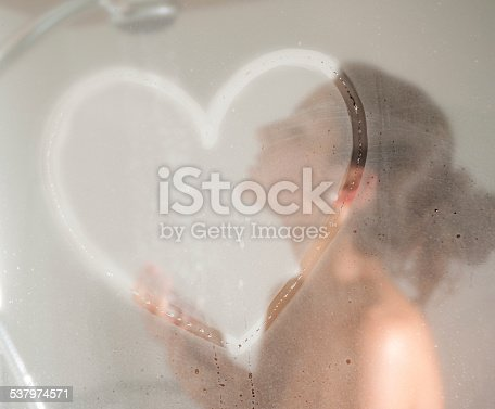 Beautiful girl showering with a drawn heart on the steamy shower glass door. Converted from RAW.