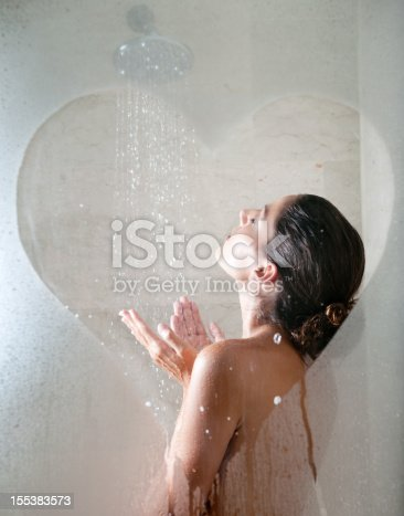 Beautiful girl showering with a drawn heart on the steamy shower glass door. Converted from RAW. Nikon D3X.