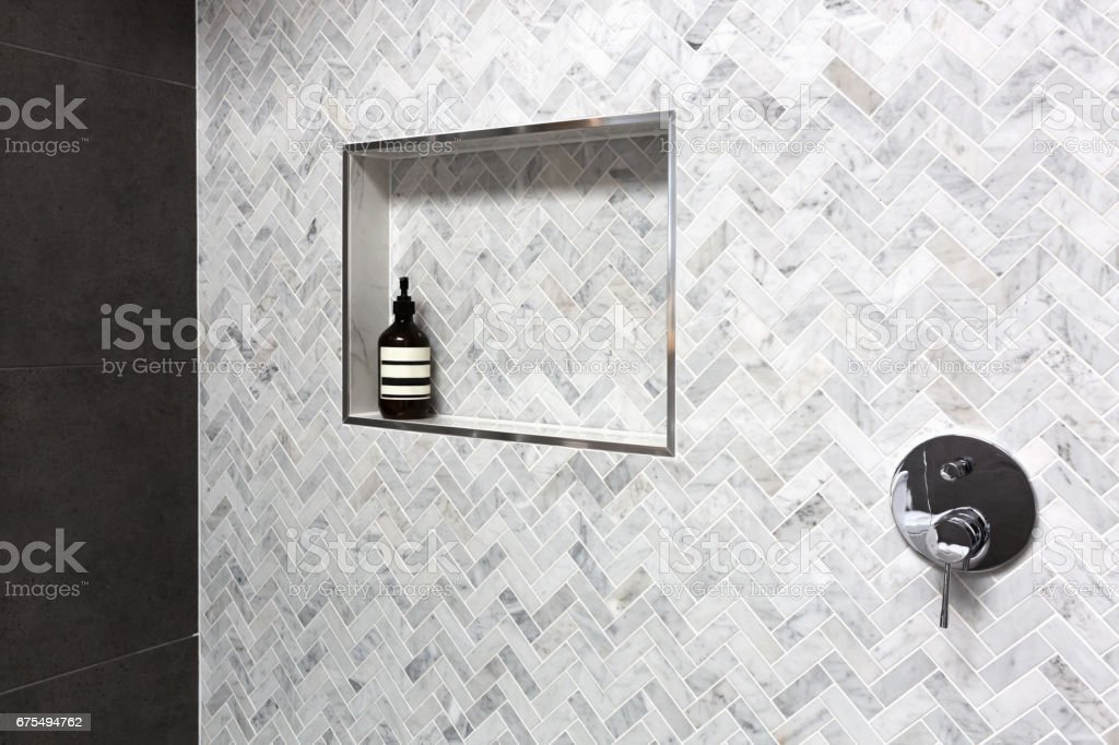 Shower shelf detail in wall of herringbone marble tiles stock photo