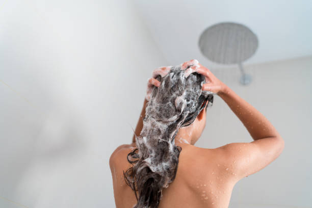 Shower woman washing hair showering in bathroom Shower woman washing hair showering in bathroom at home. Unrecognizable person from behind rinsing shampoo and conditioner from her long hair in warm bath with modern ceiling rain water nozzle head. dandruff stock pictures, royalty-free photos & images