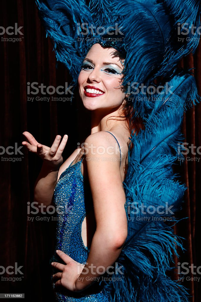 Showgirl on dark stage wearing a outfit made of feathers stock photo