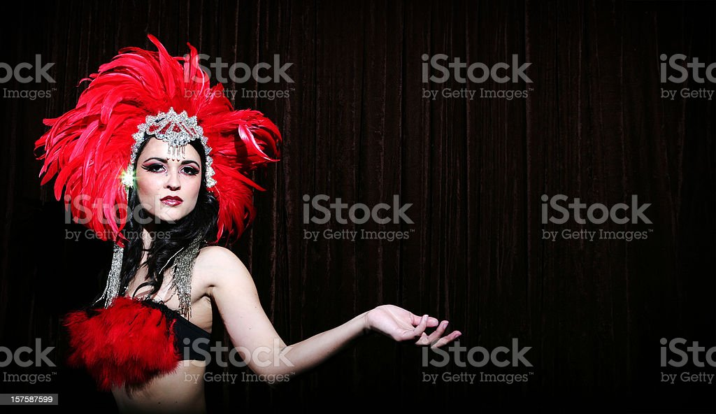 Showgirl with red feather headdress on black background stock photo