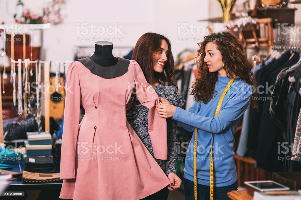 Showing a dress to a customer stock photo