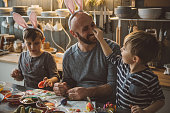 Father with sons coloring Easter eggs. Whole family is in kitchen and enjoy in holiday preparation