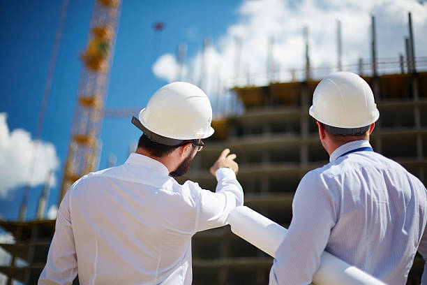 Showing building construction Rear view of architects looking at construction while one of them showing it to colleague foreman stock pictures, royalty-free photos & images