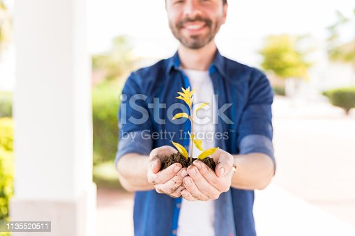 Midsection of Hispanic man showing small tree in backyard