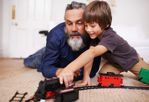 Cropped shot of a grandfather watching his grandson play with a toy train