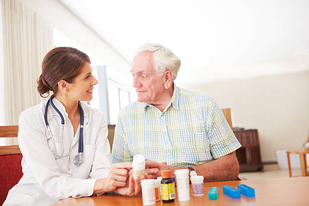 showing him when to take his meds - prescription meds stock pictures, royalty-free photos & images